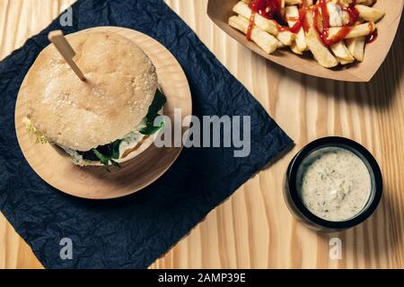top view of a gourmet vegan burger on a wooden table with french fries with ketchup in a cardboard tray and a jar with sauce, healthy food and foodie - Stock Photo