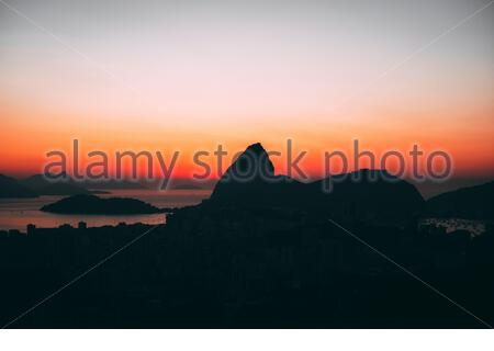The skyline of Sugarloaf Mountain and Botafogo in Rio de Janeiro, Brazil in the early morning at sunrise. Seen from Santa Teresa - Stock Photo