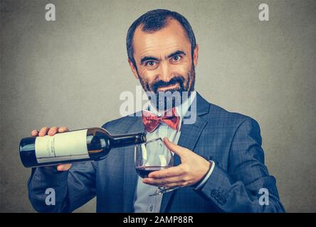A man pours some wine into a glass from a bottle looking at you camera smiling. Mixed race bearded model isolated on gray background with copy space. - Stock Photo