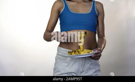 Fit female rolling measure tape around fork, healthy weight loss, nutrition - Stock Photo