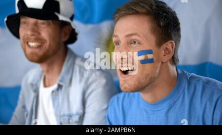 Argentina football fans watching final game on tv, celebrating team victory