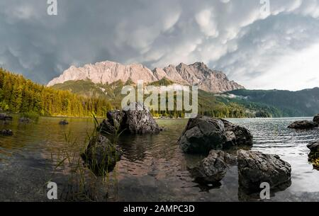 Rocks on the shore, Eibsee lake in front of Zugspitze massif with Zugspitze, sunset, dramatic Mammaten clouds, Wetterstein range, near Grainau, Upper - Stock Photo