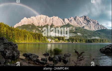 Rocks on the shore, Eibsee lake in front of Zugspitze massif with Zugspitze with rainbow, Wetterstein range, near Grainau, Upper Bavaria, Bavaria - Stock Photo