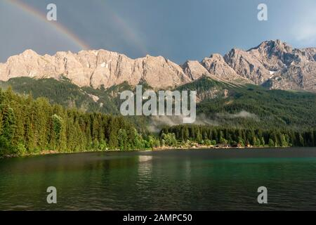 Rocks on the shore, Eibsee lake in front of Zugspitze massif with Zugspitze with double rainbow, Wetterstein range, near Grainau, Upper Bavaria - Stock Photo