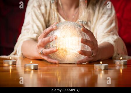 Fortune Teller with Crystal Ball on table with candles and black and red mottled background
