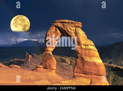 A full moon rises over Delicate Arch in Arches National Park, Utah. - Stock Photo