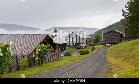 Traditional Norwegian farm with several buildings and clock tower in Innlandet region in western Norway - Stock Photo