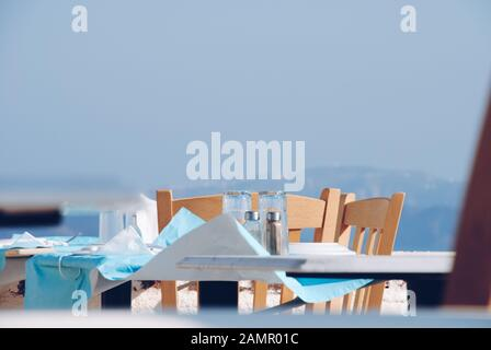 Santorini / Greece - 07 05 2013: Wooden chairs, salt and pepper in the table - Stock Photo