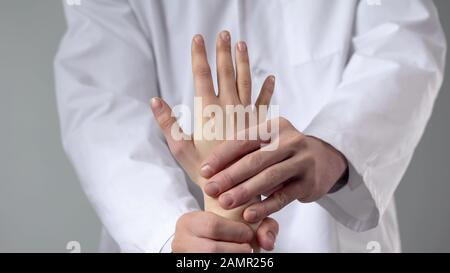 Masseur giving patient hand massage after injury, examining patients wrist - Stock Photo