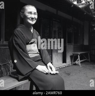 1960s, historical, elderly Japanese lady sitting outside on a bench wearing a Kimono, the traditional dress of japan. Normally made from silk, they large sleeves, go down from the shoulders to the heels and is held by an obi, a wide belt. - Stock Photo