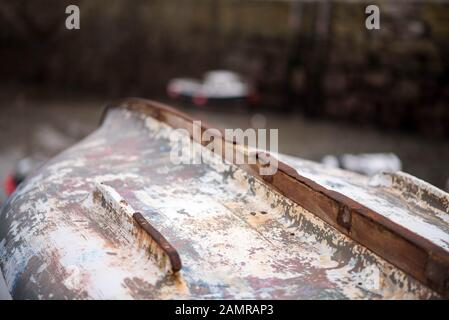 Upturned boat waiting to be worked on in a South West England fishing village - Stock Photo