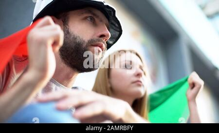 Excited football fans watching match, cheering for favorite team, final game