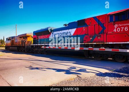 Amtrak and Ferromex diesel locomotives hauling Mexican made vehicles across the border in the US at Nogales AZ - Stock Photo