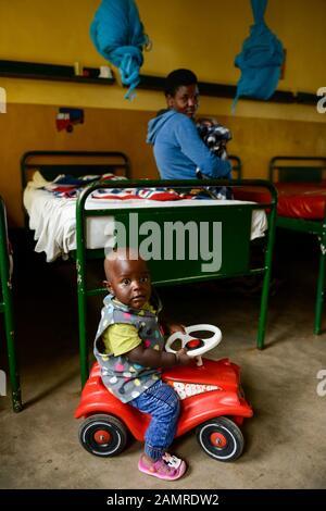 RWANDA, Butare, health center Gikonko, boy with plastic toy car Bobby Car - Stock Photo