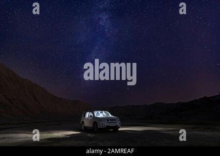 Gobustan, Azerbaijan - December 15, 2019: Japanese SUV in the desert under a starry sky - Stock Photo