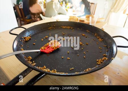 Empty Paella pan with traditional Spanish food usually prepared with rice, meat, seafood - Stock Photo