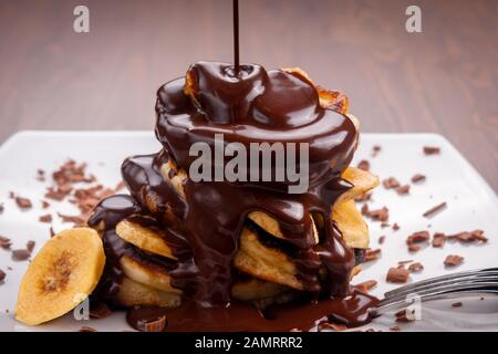 Chocolate is pouring on pancakes with banana on wooden background - Stock Photo