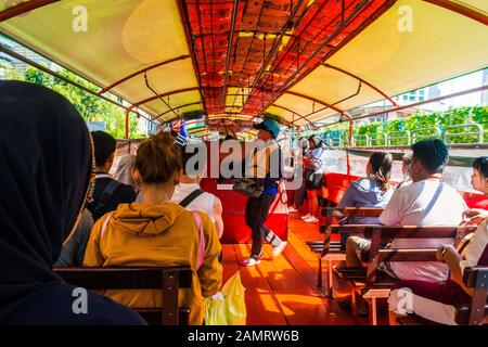 Bangkok/Thailand-05 December 2019: Inside view of a Bangkok ferry boat on Khlong saen saep canal with passengers waiting and the ticket inspector - Stock Photo