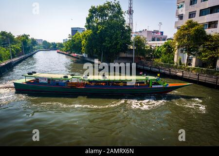 Bangkok/Thailand-05 December 2019: Colorful Bangkok ferry long boat on Khlong saen saep canal transporting people around the city. - Stock Photo