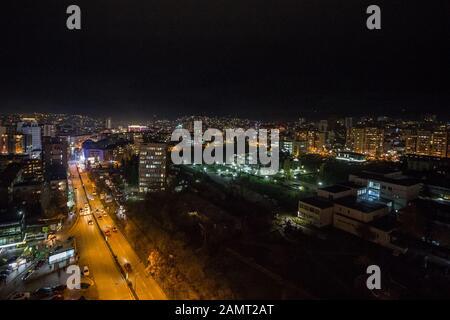 PRISHTINA, KOSOVO - NOVEMBER 11, 2016: Night view of Mother Tereza Boulevard in Prishtina with cars passing and downtown landmark like the National Li - Stock Photo
