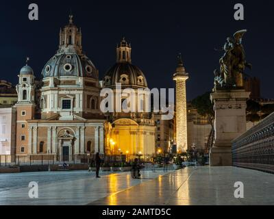 Rome, Italy - March 25, 2018: Tourists stop for photos of the ancient and Renaissance architecture of Piazza Venezia in Rome at night. - Stock Photo