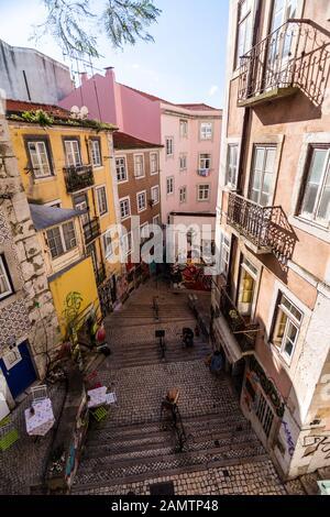 Lisbon, Portugal - March 11, 2016: Apartment buildings cast shadows on a steep, nwrrow alleyway on a hillside of Lisbon's Baixa neighbourhood. - Stock Photo