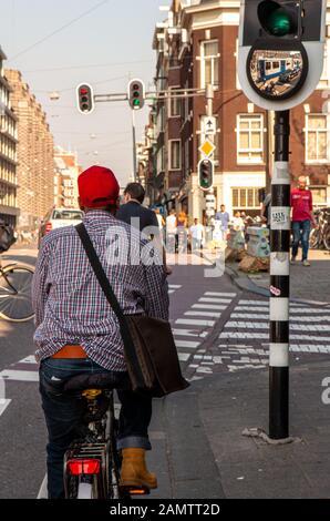 Amsterdam, Netherlands - October 2, 2011: A cyclist waits at a traffic signal in the centre of the city of Amsterdam. - Stock Photo
