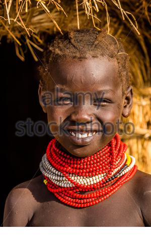 Nyangatom tribe girl in front of her famiy's hut, Omo Valley, Ethiopia. - Stock Photo