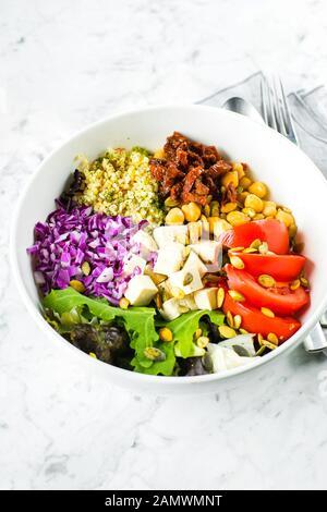 Vegetarian buddha bowl. Raw vegetables, tofu and bulgur in white bowl. Vegetarian, healthy, detox food concept - Stock Photo