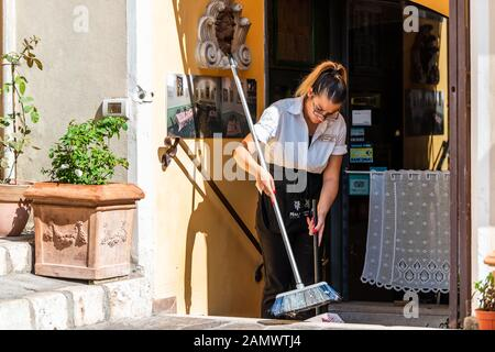 Perugia, Italy - August 29, 2018: Historic old Etruscan buildings of town village with woman worker in restaurant cafe cleaning with broom