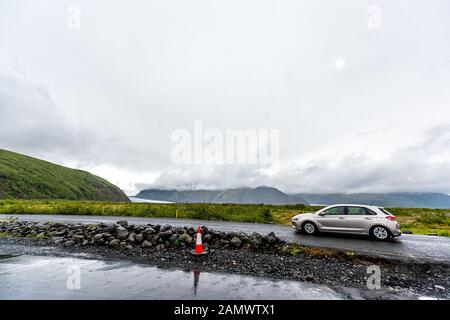 Skaftafell, Iceland - June 15, 2018: Car on road near national park and Svartifoss waterfall hike with people inside vehicle near city of Hof on cloud