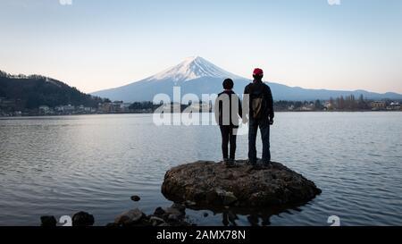 A couple enjoying Sunrise view of Mt Fuji on the northern shore of Lake Kawaguchiko in Japan - Stock Photo