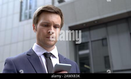 Worried businessman receiving bad news on smartphone, desperate situation, fail - Stock Photo