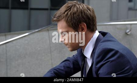 Pensive male sitting on staircase near office building, worrying about startup - Stock Photo