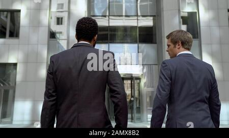 Office workers in suits going to work in modern business center, white collars - Stock Photo