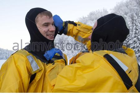 U.S. Air Force Airman 1st Class Marcus Davidson, right, assists Staff Sgt. Michael Hermann don a survival suit before conducting ice rescue training at Six Mile Lake on Joint Base Elmendorf-Richardson, Alaska, Jan. 11, 2020. The training, conducted in minus 15 degree Fahrenheit weather, taught the JBER firefighters the knowledge and skills necessary for safe rescue and recovery operations in, on and around ice and cold water. After completion of a classroom session, practical skills evaluation and a written examination the fire protection specialists were certified as ice rescue technicians. D - Stock Photo
