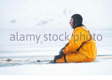 U.S. Air Force Staff Sgt. Joseph Dempsey, a fire protection specialist with the 673d Civil Engineer Squadron, momentarily rests after pulling himself from open water during ice rescue training at Six Mile Lake on Joint Base Elmendorf-Richardson, Alaska, Jan. 11, 2020. The training, conducted in minus 15 degree Fahrenheit weather, taught the JBER firefighters the knowledge and skills necessary for safe rescue and recovery operations in, on and around ice and cold water. After completion of a classroom session, practical skills evaluation and a written examination the fire protection specialists - Stock Photo