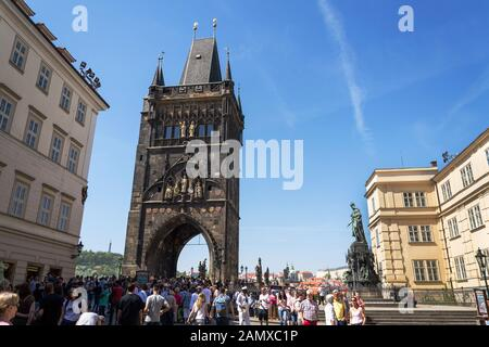 PRAGUE, CZECH REPUBLIC - APRIL 21 2018: Tourist walking on the Charles Bridge with Town Bridge Tower in background on April 21, 2018 in Prague, Czech - Stock Photo