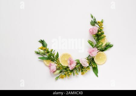 Creative arrangement of pink and yellow flowers with lemons on a white background with a copy space