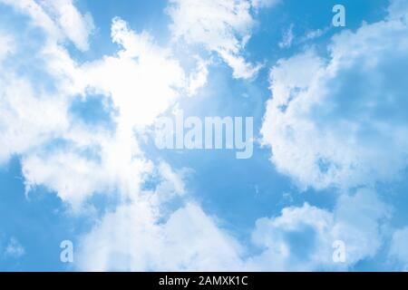 The rays of the sun break through the clouds, a clear blue sunny sky. Cloudscape Background Backdrop - Stock Photo