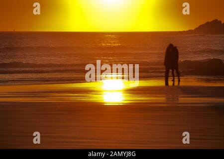 Couple kissing on Croyde Bay Beach at Sunset - Stock Photo