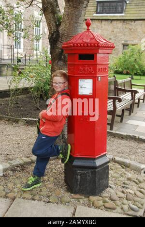 Red Victorian Pillar Box at  Durham Cathedral County Durham UK with young boy in red top leaning against pillar box - Stock Photo