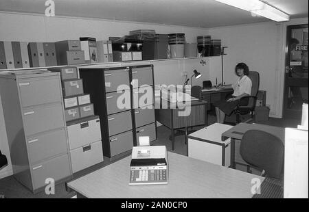 1986, historical, a female clerical worker at a desk in an low-ceiling office, surrounded office supplies and stacks of metal filing cabinets, England, UK. - Stock Photo