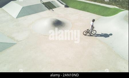 Top minimal view of bmx biker training in skate park outdoor - Young man performing tricks with special bicycle - Focus on man - Extreme sport concept