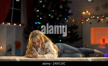 Girl making wish list before Christmas eve, writing letter to Santa Claus, magic - Stock Photo