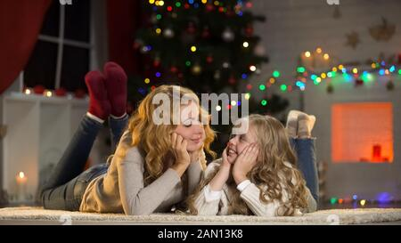 Young mother and daughter lying under Christmas tree, looking at each other - Stock Photo
