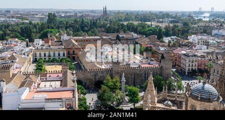 A view, from the Giralda, of the Main Sacristy of Seville Cathedral. Plaza del Triunfo and Real Alcázar with the distant towers of Plaza De Espana. - Stock Photo