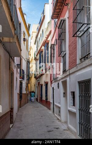 Colourful buildings line a narrow alley in Seville's historic Jewish Quarter.