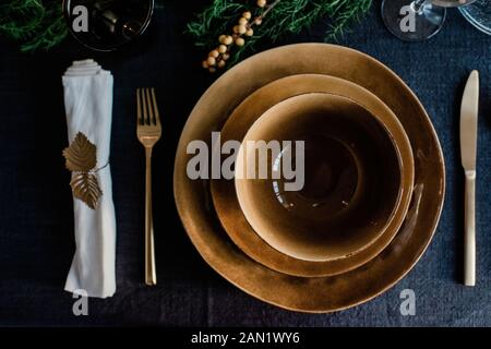 gold plates and bowls with gold cutlery on a decorated dinner table - Stock Photo