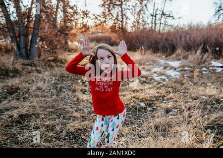 young girl making a silly face wearing fun christmas clothes - Stock Photo